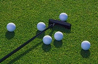Putter and golf balls on green