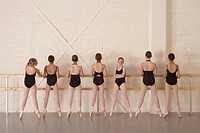Seven girls (11-13) standing on toes at barre in ballet class