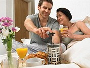 Couple having breakfast in bed, man pushing down coffee plunger