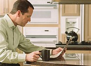 Mature man drinking coffee in kitchen, reading newspaper, side view