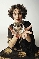 Woman holding out crystal ball, portrait