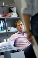 Man sitting at desk facing male colleague (focus on man)