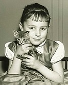 Girl (8-9) holding kitten at home, (B&W), portrait