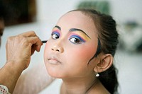 8 years old female dancer at her dance teacher home for make-up and practising Legong Kraton dance. Gyanar. Island of Bali . Indonesia