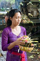 Woman making offerings in a temple. Ubud. Island of Bali . Indonesia