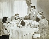 Family sitting around table, having meal, children (4-5) (6-7), (B&W)