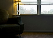 Warm light from a lamp illuminates an empty green chair inside an apartment on a rainy day. Chapel Hill. North Carolina. USA