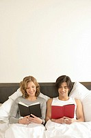 Young couple sitting in a bed, reading