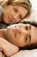 Young couple lying in a bed, man looking at camera