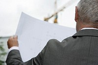 Manager with architect's plan in hands, rear view