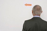 Elderly manager looking at directional arrow on the wall, rear view