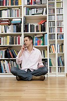Man sitting in front of a shelf and using a mobile phone