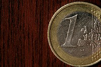 Single Euro coin on wooden underlay (part of), close-up