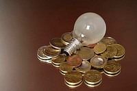 Electric bulb on a stack of Euro-coins, close-up