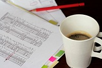 Paper cup with coffee standing next to documents and a colored crayon