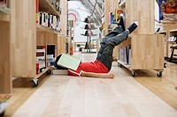 Boy covering face with a book and lying inside a library, fully-released