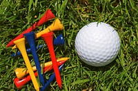 Golf ball and wooden tees on grass