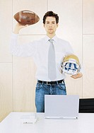 Young man holding football and football helmet, portrait