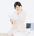 Young businesswoman sitting on desk, using telephone