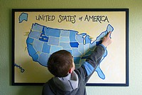 Boy, 5, pointing to a homemade map of USA on wall in his bedroom