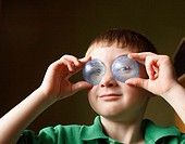 Boy, age five, holding clear blue plastic pieces to his eyes