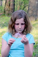 10-year-old girl holding purple wildflower in right hand, petal from flower in left hand, looking a bit concerned, light turquoise short-sleeved shirt...