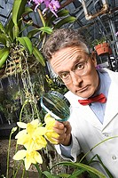 Scientist with magnifying glass and flowers