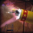 Businessman launching from circus cannon