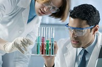 Man and woman working with chemicals in laboratory.