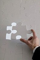 Hand placing puzzle piece into jigsaw puzzle.