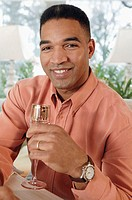 Man holding wine glass, portrait.