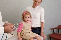 Little girl with mother and medical professional, portrait
