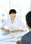Businesswoman talking to colleague across table