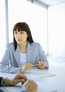 Businesswoman sitting at table looking attentively toward colleague