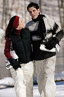 Couple outdoors carrying ice skates