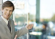 Young businessman smiling at camera and gesturing (thumbnail)