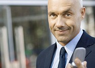 Businessman holding out cell phone
