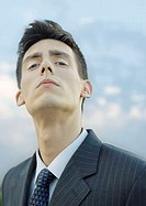 Young businessman, looking down at camera, portrait (thumbnail)