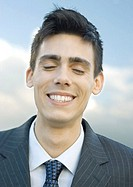 Young businessman, eyes closed, portrait