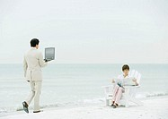 Woman sitting reading newspaper on beach as businessman carrying open laptop approaches