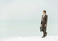 Businesswoman walking on beach
