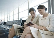 Two women sitting in airport lounge together