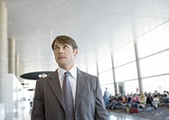 Businessman in airport, looking up