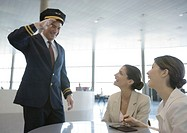 Airline pilot saluting two female travelers