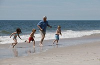 Grandfather with grandchildren at beach