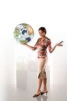 Woman holding globe and credit card, portrait.