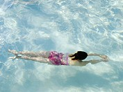 Girl swimming underwater in a swimming pool.
