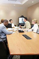 Business executives talking in a video conference room