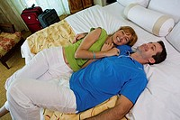 High angle view of a young couple lying on the bed and smiling