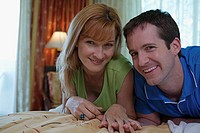 Portrait of a young couple lying on the bed and smiling